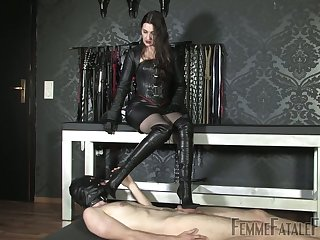 Mistress in black suit Victoria Valente punishes dick of nude submissive